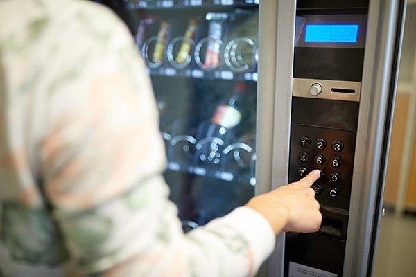 donna che schiaccia un pulsante per ritirare delle merendine da un distributore automatico