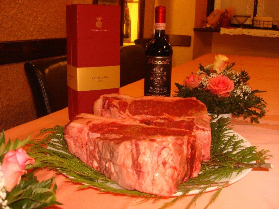 fiorentina cruda sul tavolo con bottiglia di vino