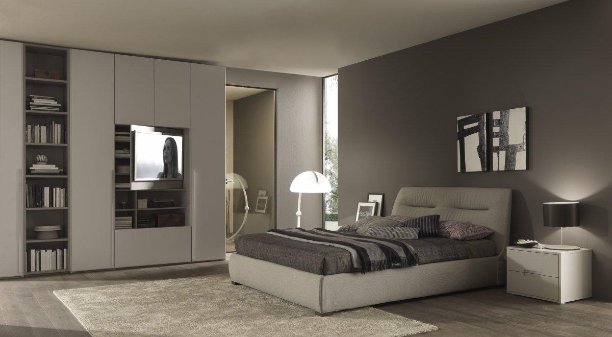 Una camera con un letto matrimoniale con la testata imbottita
