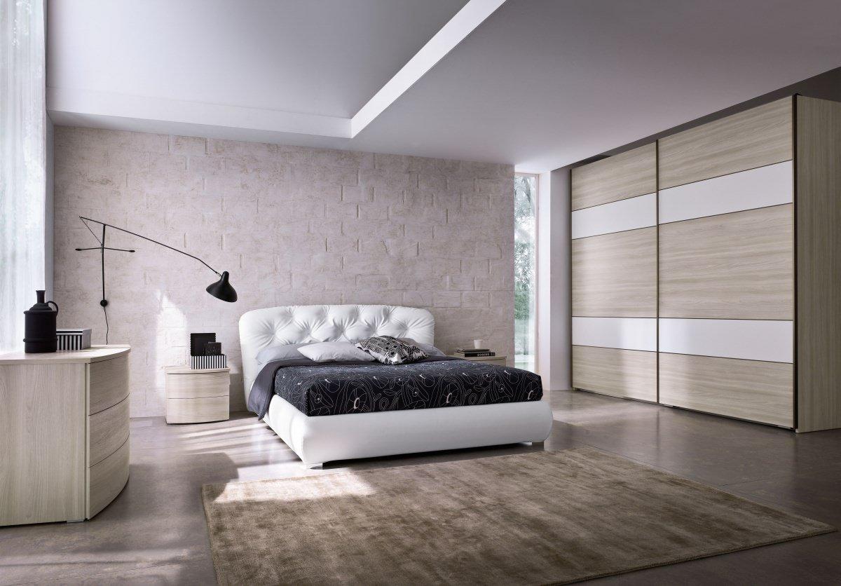 Una camera con un letto di color bianco e sulla destra un armadio con le ante scorrevoli