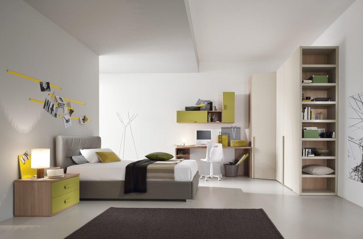 una camera con un letto di color grigio, una scrivania e un armadio