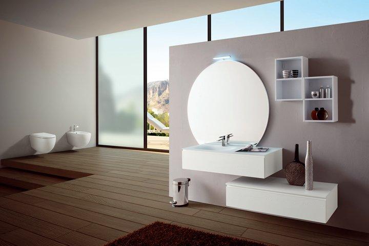 un bagno con uno specchio rotondo e un lavabo rettangolare