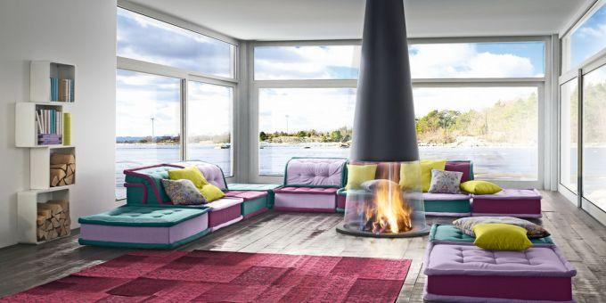 un divano angolare di color rosa, lilla e verde