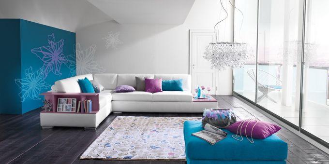 un divano angolare di color bianco con dei cuscini di color azzurro e viola