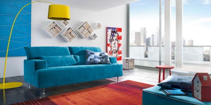 un divano di color azzurro e accanto una lampada da terra di color giallo