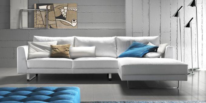 un divano angolare di color bianco e un pouf di color azzurro davanti