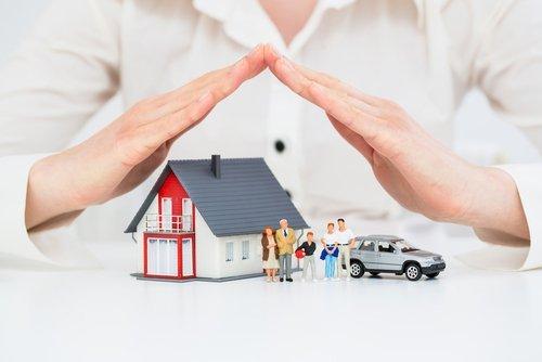 mani di una donna che coprono un modellino di casa con famiglia e automobile