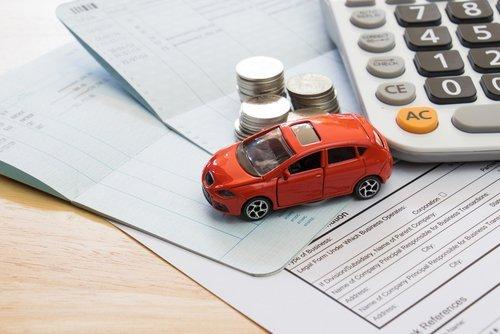 modellino di automobile vicino a delle monete impilate e una calcolatrice
