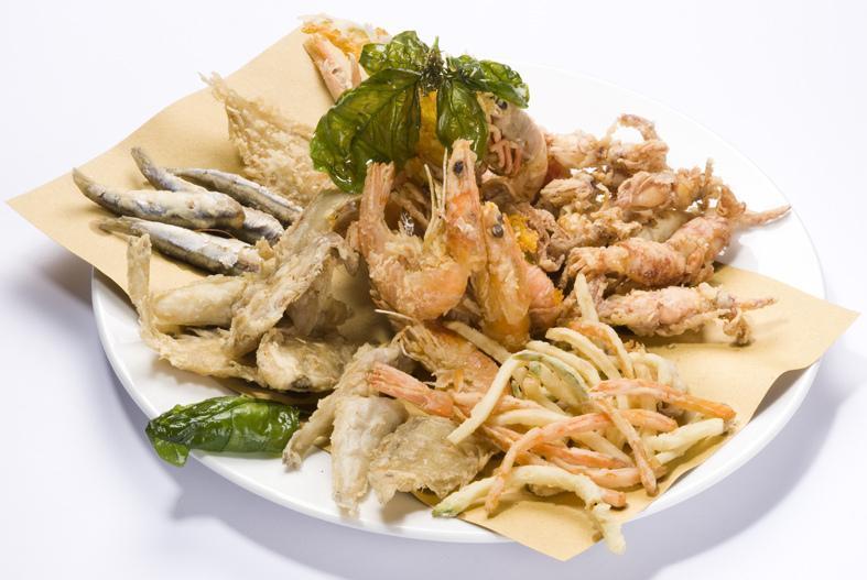 un piatto di fritto misto di pesce con sopra una foglia di basilico