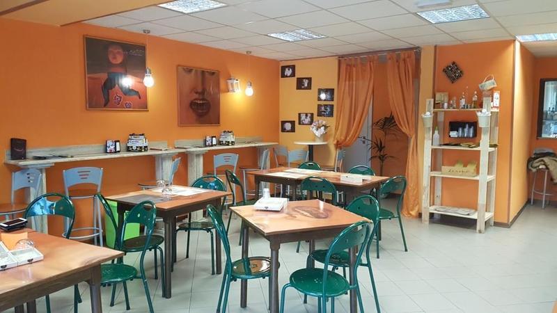 interno del locale con vista del bancone con le vetrine, un uomo dietro al bancone e dei tavoli con delle sedie verdi