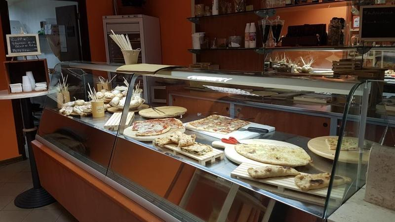 vista di un bancone vetrina all'interno di un negozio con focacce e pizze sui taglieri