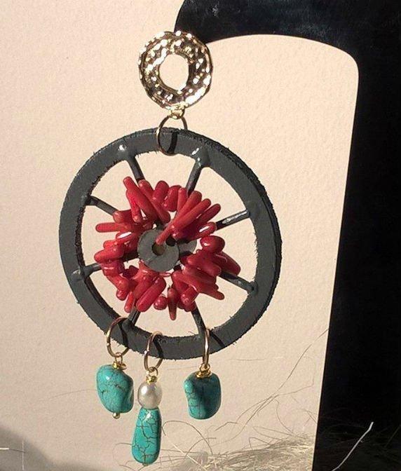 un orecchino con delle pietre azzurre e rosse