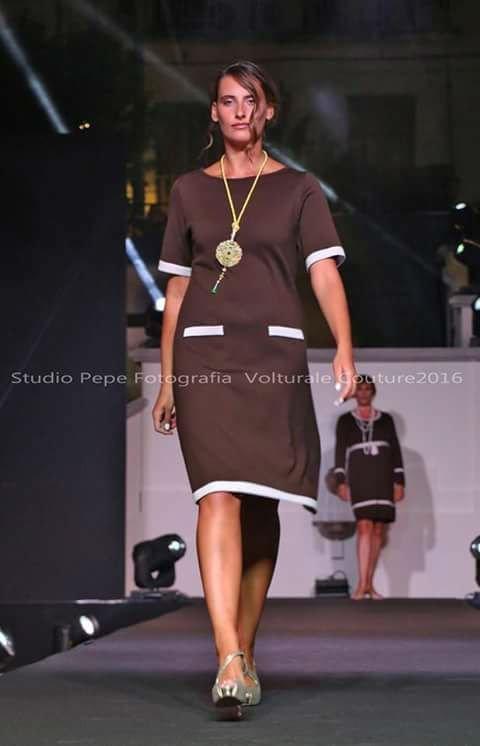 una modella con dei vestiti beige e una collana dorata
