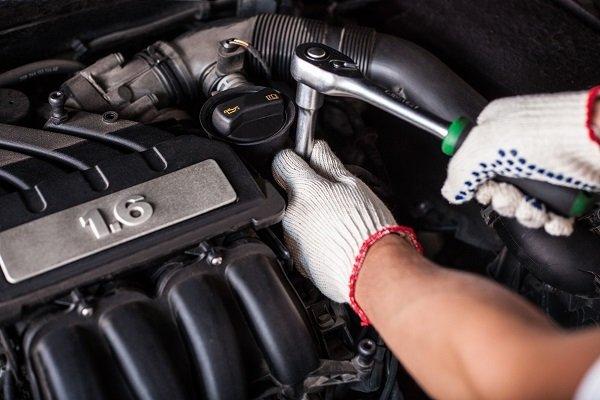 meccanico mentre ripara il motore di un'auto