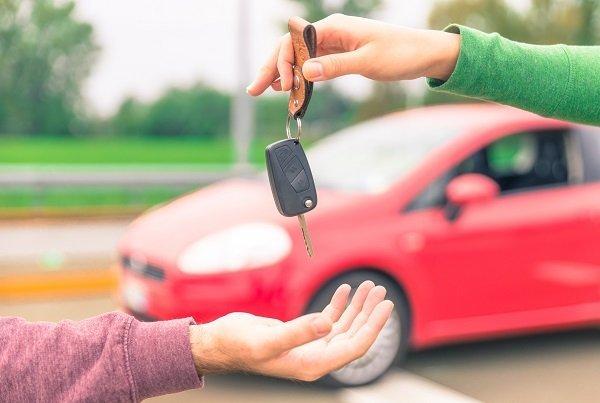 una mano che passa delle chiavi di un'auto a un'altra mano