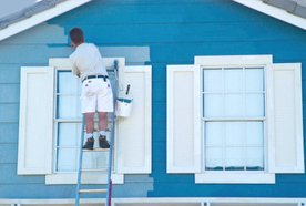 A person painting the front of a house