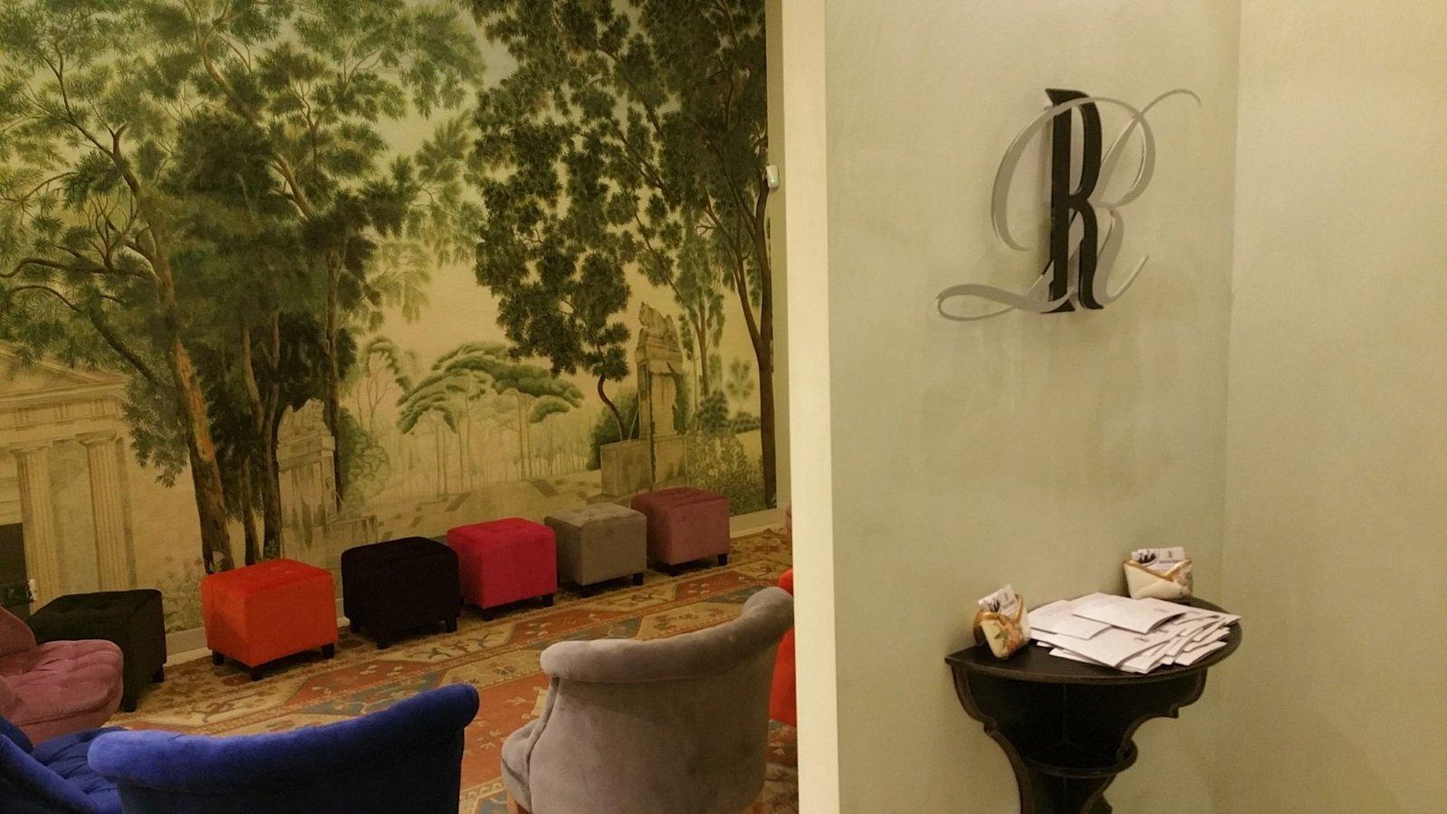 una stanza con delle poltrone, dei pouf e dei disegni di alcuni alberi