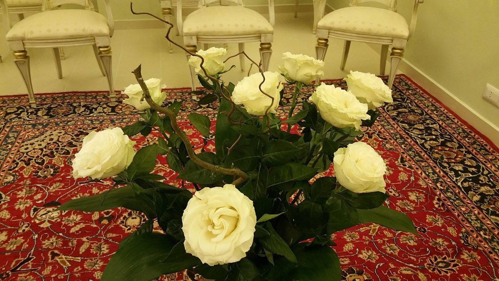 un vaso di rose gialle in una stanza con un tappeto e delle sedie