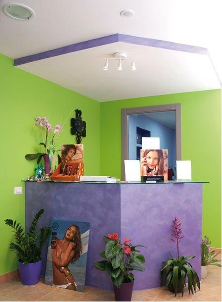 un banco di una reception viola con delle foto e dei vasi di fiori