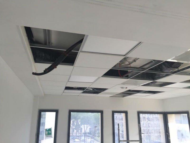 delle tubature che fuoriescono da un soffitto a pannelli non ancora finito
