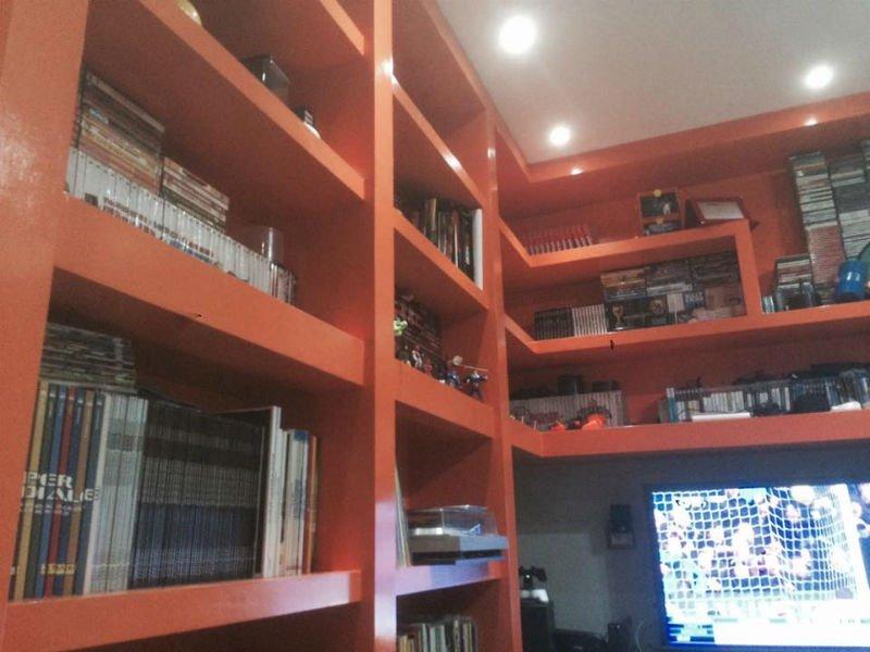 un armadio a muro di color rosso con delle mensole, libri e altro