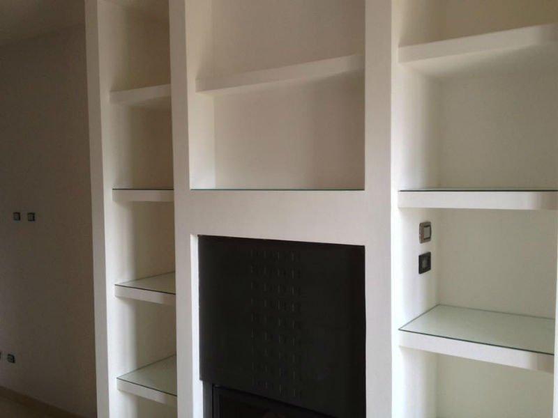 un mobile a muro con delle mensole e sotto una stufa