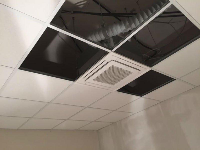 dei condotti d'aria visibili attraverso un soffitto a pannelli non ancora finito