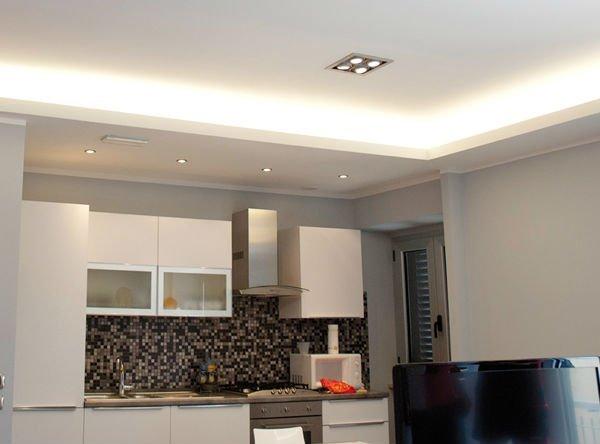 una cucina con mobili bianchi e parete a mosaico con piastrelle bianche e nere