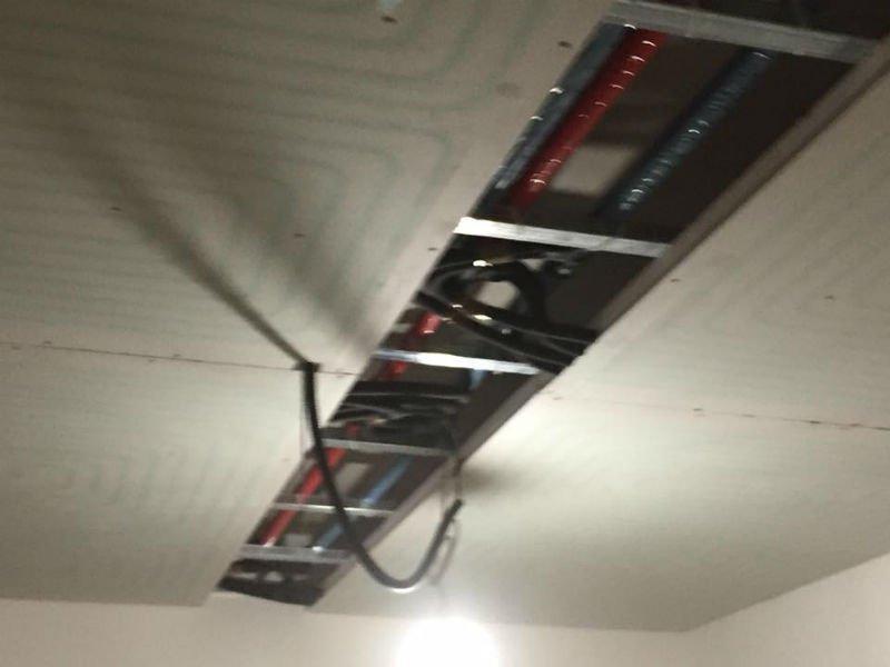 dei tubi  visibili in un soffitto a pannelli non ancora completato