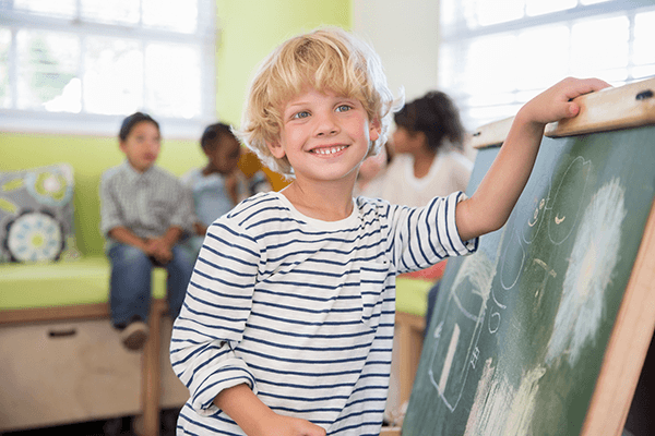 Boy beside a blackboard