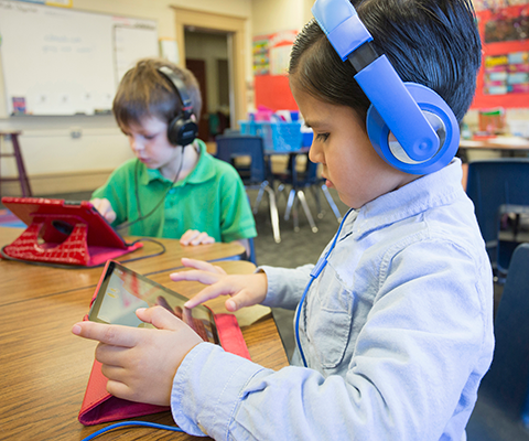 children with headphones and tablets