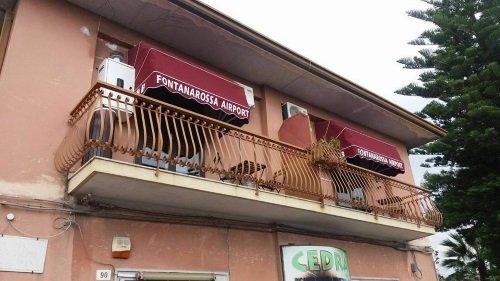 Un balcone con due tende da sole di color bordeaux con scritto Fontanarossa Airport