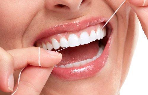 filo interdentale nella bocca di una donna