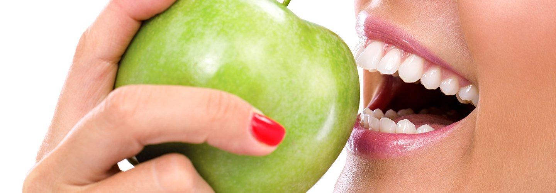 giovane donna che mangia mela verde