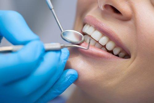 dentista mentre controlla denti di un paziente
