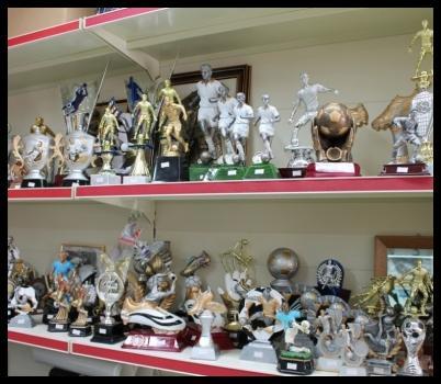 vista laterale di scaffali di negozio con coppe e trofei