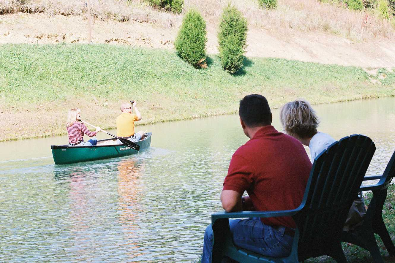 Couple sitting at pond looking at canoe