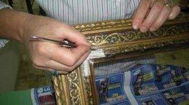 restauratore dipinge una cornice