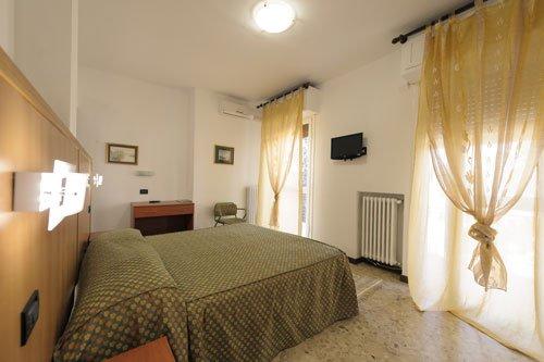 un letto matrimoniale e vista delle finestre con delle tende gialle in una stanza