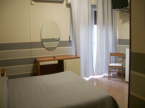 una piccola scrivania, sopra uno specchio e un letto in una stanza