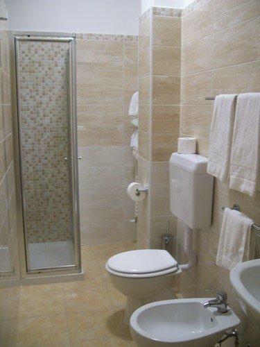 un bagno con sulla destra wc,bidet e di fronte un box doccia