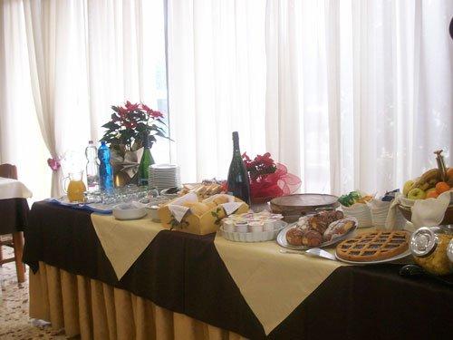 un buffet con con una crostata, brioches, una bottiglia e altre