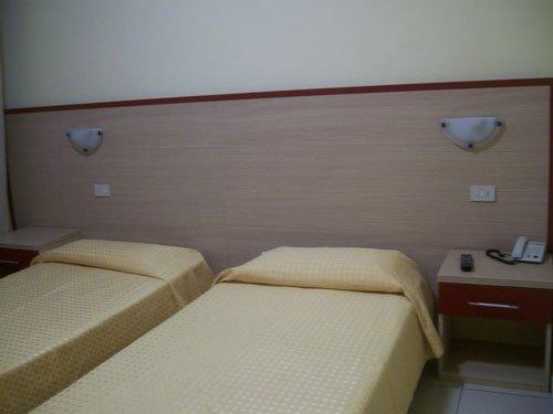 due letti singoli e sulla sinistra un comodino in una stanza