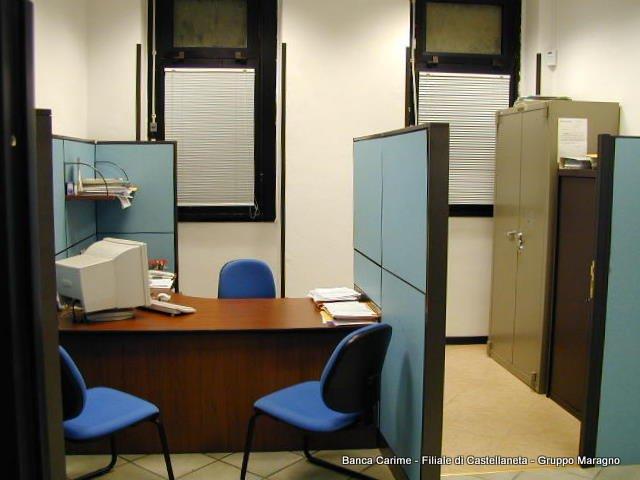 una stanza con una scrivania , delle sedie e una fotocopiatrice