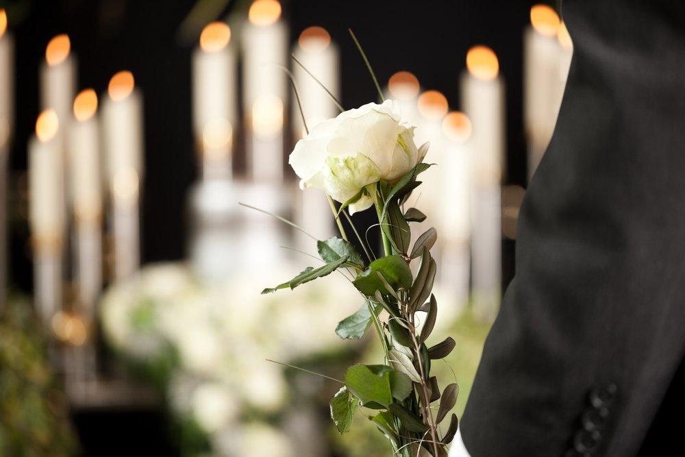 uomo con fiore bianco a un funerale