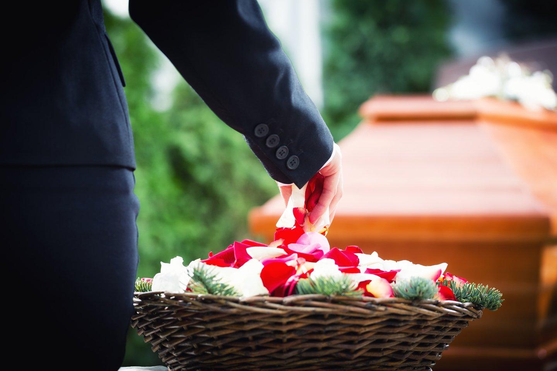 donna con petali di fiori in mano vicino a una bara