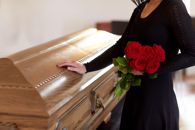 donna con mazzo di rose ad un funerale