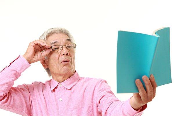 un signore con gli occhiali mentre cerca di leggere un libro tenendolo distante