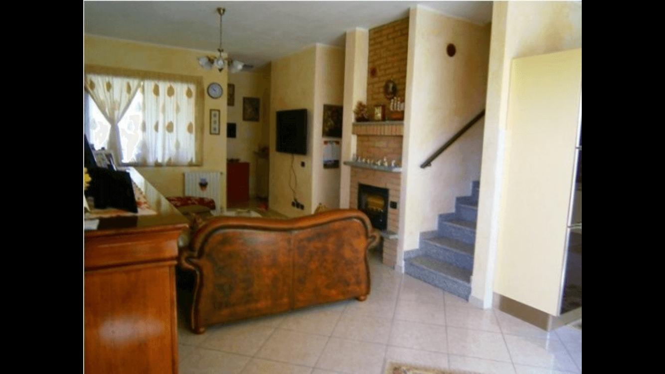 soggiorno con divano e scale per salire al piano superiore