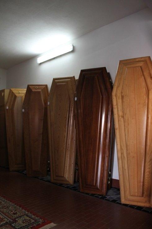 delle bare in legno classico appoggiate al muro